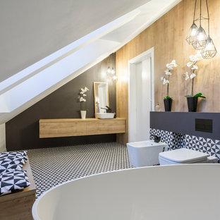 Foto de cuarto de baño azulejo de dos tonos, contemporáneo, con armarios con paneles lisos, puertas de armario de madera oscura, bañera exenta, bidé, baldosas y/o azulejos negros, paredes negras, lavabo sobreencimera, encimera de madera, suelo multicolor y encimeras marrones
