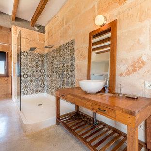 Imagen de cuarto de baño principal, mediterráneo, con armarios abiertos, puertas de armario de madera oscura, ducha abierta, paredes rosas, lavabo sobreencimera, encimera de madera, suelo beige y ducha abierta