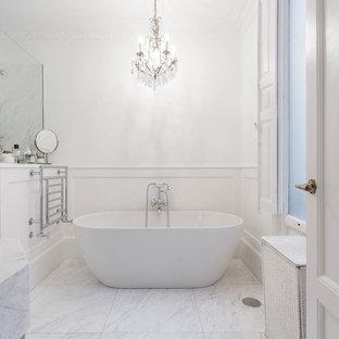 Imagen de cuarto de baño principal, tradicional, de tamaño medio, con bañera exenta, combinación de ducha y bañera, paredes blancas, suelo de mármol, suelo blanco y ducha abierta