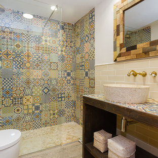 Design ideas for a medium sized mediterranean ensuite bathroom in Other with open cabinets, an alcove shower, a wall mounted toilet, multi-coloured tiles, ceramic tiles, multi-coloured walls, a vessel sink, tiled worktops, dark wood cabinets, beige floors, an open shower and multi-coloured worktops.