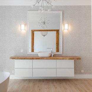 Diseño de cuarto de baño principal, actual, grande, con paredes beige, suelo beige, armarios con paneles lisos, puertas de armario blancas, bañera exenta, suelo de madera clara, lavabo tipo consola, encimera de madera y encimeras marrones