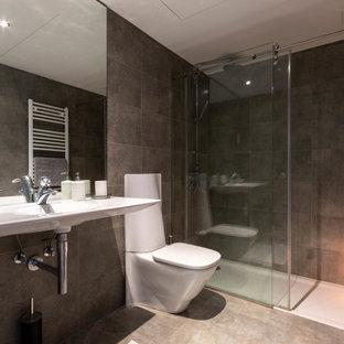 Ejemplo de cuarto de baño único, contemporáneo, de tamaño medio, con ducha esquinera, sanitario de una pieza, baldosas y/o azulejos grises, baldosas y/o azulejos de porcelana, suelo de baldosas de porcelana, lavabo suspendido, suelo gris y ducha con puerta con bisagras