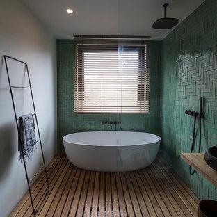 Scandi wet room bathroom in Amsterdam with a freestanding bath, green tiles, ceramic tiles, white walls, medium hardwood flooring, a vessel sink, wooden worktops, brown floors, an open shower and brown worktops.