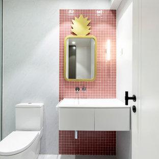 Imagen de cuarto de baño con ducha, actual, con armarios con paneles lisos, puertas de armario blancas, sanitario de dos piezas, baldosas y/o azulejos rosa, baldosas y/o azulejos en mosaico, lavabo integrado y encimeras blancas