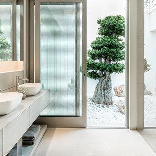 Ejemplo de cuarto de baño principal, marinero, con armarios con paneles lisos, puertas de armario de madera clara, lavabo sobreencimera, encimera de madera y suelo beige