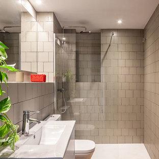 Foto de cuarto de baño con ducha, actual, de tamaño medio, con puertas de armario blancas, ducha a ras de suelo, baldosas y/o azulejos de cerámica, suelo de baldosas de porcelana, encimeras blancas, armarios con paneles lisos, baldosas y/o azulejos grises, lavabo integrado, suelo beige y ducha abierta