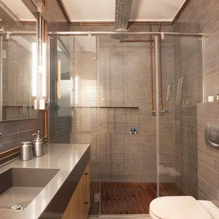 Idee per una stanza da bagno con doccia industriale di medie dimensioni con ante lisce, ante in legno scuro, doccia alcova, WC monopezzo, piastrelle grigie, piastrelle in ceramica, lavabo integrato, top in acciaio inossidabile e porta doccia a battente