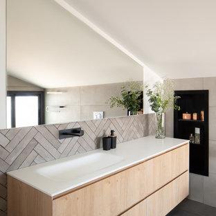 Diseño de cuarto de baño contemporáneo con armarios con paneles lisos, puertas de armario de madera clara, baldosas y/o azulejos beige, paredes blancas, lavabo integrado, suelo gris y encimeras blancas