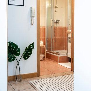 Ispirazione per una piccola stanza da bagno con doccia contemporanea con ante a filo, ante bianche, doccia ad angolo, WC a due pezzi, piastrelle arancioni, piastrelle in ceramica, pareti arancioni, pavimento in terracotta, lavabo a bacinella, top in superficie solida, pavimento arancione, porta doccia scorrevole e top bianco