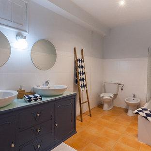 Ejemplo de cuarto de baño rústico con puertas de armario azules, baldosas y/o azulejos blancos, suelo de baldosas de cerámica, encimera de vidrio y suelo naranja