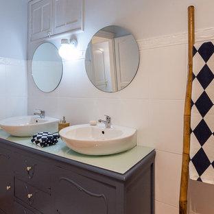 Modelo de cuarto de baño rústico con puertas de armario azules, baldosas y/o azulejos blancos, suelo de baldosas de cerámica, encimera de vidrio y suelo naranja