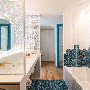 Modelo de cuarto de baño actual con armarios abiertos, bañera encastrada, baldosas y/o azulejos azules, baldosas y/o azulejos blancos, lavabo integrado, suelo azul, encimeras blancas, combinación de ducha y bañera y paredes blancas