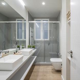 Modelo de cuarto de baño con ducha, contemporáneo, de tamaño medio, con puertas de armario blancas, ducha empotrada, urinario, paredes grises, encimera de cuarzo compacto, suelo marrón, ducha con puerta con bisagras, armarios abiertos, baldosas y/o azulejos grises, baldosas y/o azulejos de porcelana, lavabo sobreencimera y encimeras blancas