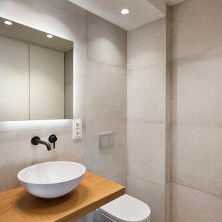 Diseño de cuarto de baño moderno con baldosas y/o azulejos beige, paredes beige, suelo de madera en tonos medios, lavabo sobreencimera, encimera de madera, suelo marrón y encimeras marrones