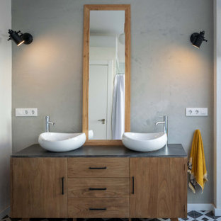 Inspiration for a medium sized mediterranean ensuite bathroom in Valencia with freestanding cabinets, medium wood cabinets, a one-piece toilet, black and white tiles, ceramic tiles, grey walls, a vessel sink, grey floors, grey worktops and double sinks.