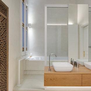Foto de cuarto de baño mediterráneo con bañera empotrada, lavabo sobreencimera, encimera de madera, armarios con paneles lisos, puertas de armario de madera clara, paredes grises, suelo gris y encimeras beige