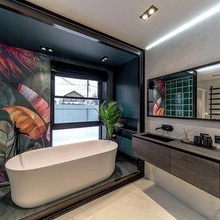 Modelo de cuarto de baño principal, actual, con armarios con paneles lisos, puertas de armario grises, bañera exenta, baldosas y/o azulejos grises, suelo gris y encimeras grises