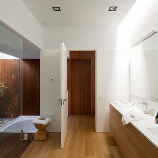 Ejemplo de cuarto de baño actual con suelo de madera en tonos medios, suelo marrón, armarios con paneles lisos, puertas de armario de madera oscura, paredes blancas, lavabo integrado y encimeras blancas