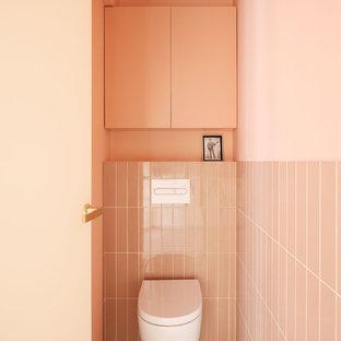 Foto de cuarto de baño actual con sanitario de pared, baldosas y/o azulejos rosa, paredes rosas y suelo gris