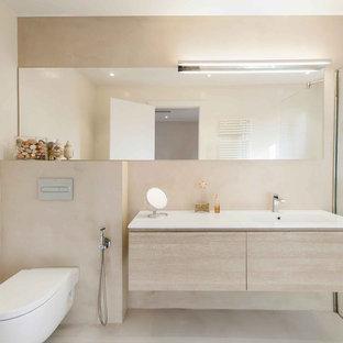 Imagen de cuarto de baño con ducha, escandinavo, de tamaño medio, con armarios con paneles lisos, puertas de armario de madera clara, ducha a ras de suelo, sanitario de pared, paredes grises, suelo de cemento, lavabo integrado, suelo gris y encimeras blancas