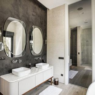 Foto de cuarto de baño principal, contemporáneo, con armarios con paneles lisos, puertas de armario grises, paredes negras, suelo de madera clara, lavabo sobreencimera y encimeras blancas
