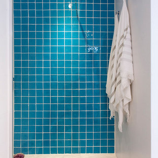 This is an example of a small mediterranean bathroom in Barcelona with open cabinets, medium wood cabinets, a two-piece toilet, blue tiles, stone tiles, white walls, travertine flooring, beige floors and an open shower.