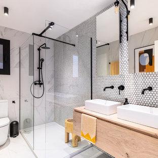 Imagen de cuarto de baño principal, actual, de tamaño medio, con armarios con paneles lisos, puertas de armario de madera clara, ducha abierta, baldosas y/o azulejos blancos, baldosas y/o azulejos en mosaico, lavabo sobreencimera, encimera de madera, suelo gris, ducha abierta y encimeras beige