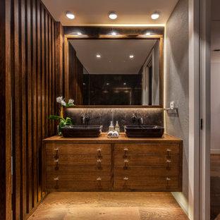 Diseño de cuarto de baño con ducha, contemporáneo, de tamaño medio, con armarios con paneles lisos, puertas de armario de madera oscura, baldosas y/o azulejos negros, baldosas y/o azulejos grises, paredes grises, suelo de madera en tonos medios, lavabo sobreencimera, encimera de madera, suelo marrón y encimeras marrones