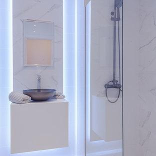 Foto de cuarto de baño actual con armarios con paneles lisos, puertas de armario blancas, ducha a ras de suelo, paredes blancas, lavabo sobreencimera, suelo blanco, ducha abierta y encimeras blancas