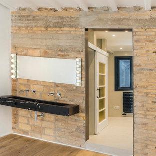 На фото: главная ванная комната среднего размера в стиле лофт с открытыми фасадами, бежевыми фасадами, японской ванной, душем над ванной, инсталляцией, мраморной плиткой, бежевыми стенами, бетонным полом, подвесной раковиной, мраморной столешницей, бежевым полом, открытым душем и черной столешницей