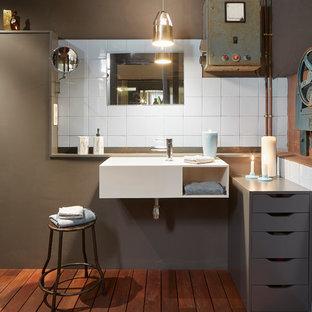 Ejemplo de cuarto de baño urbano con paredes grises, suelo de madera en tonos medios, lavabo suspendido, suelo marrón y baldosas y/o azulejos blancos