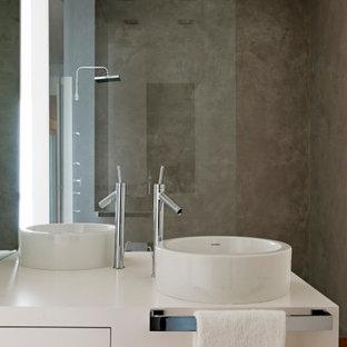 Modelo de cuarto de baño industrial con armarios con paneles lisos, puertas de armario blancas, paredes grises, suelo de madera en tonos medios, lavabo sobreencimera y suelo marrón
