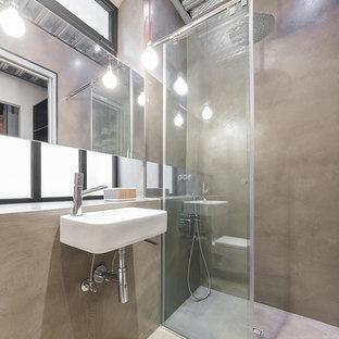 Modelo de cuarto de baño con ducha, urbano, de tamaño medio, con ducha a ras de suelo, paredes grises, suelo de cemento, lavabo suspendido y ducha abierta