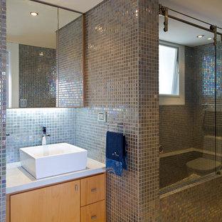 Foto de cuarto de baño contemporáneo con baldosas y/o azulejos grises, baldosas y/o azulejos con efecto espejo, lavabo sobreencimera, ducha con puerta corredera, encimeras blancas, armarios con paneles lisos, puertas de armario de madera oscura y suelo beige