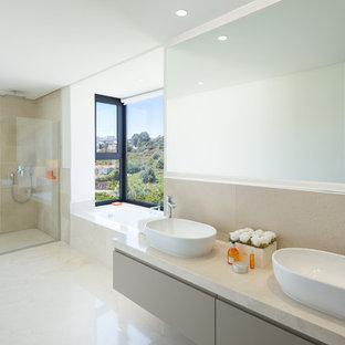 Modelo de cuarto de baño principal, contemporáneo, con armarios con paneles lisos, ducha a ras de suelo, baldosas y/o azulejos beige, paredes beige, lavabo sobreencimera, encimeras beige, puertas de armario beige, bañera encastrada, suelo beige y ducha abierta