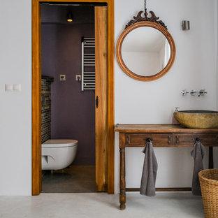 Kleines Mediterranes Badezimmer mit Aufsatzwaschbecken, verzierten Schränken, hellbraunen Holzschränken, Wandtoilette, lila Wandfarbe, Betonboden und Waschtisch aus Holz in Malaga