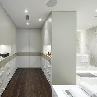 Diseño de cuarto de baño actual con armarios con paneles lisos, puertas de armario blancas, bañera exenta, baldosas y/o azulejos de mármol y encimeras blancas