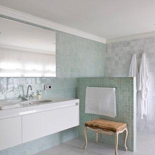 Ejemplo de cuarto de baño principal, mediterráneo, con puertas de armario blancas, baldosas y/o azulejos verdes, baldosas y/o azulejos grises, ducha abierta, encimeras blancas, armarios con paneles lisos, paredes multicolor, lavabo bajoencimera y suelo gris