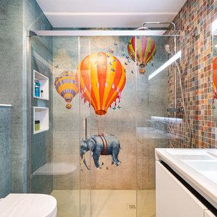 На фото: детская ванная комната среднего размера в современном стиле с разноцветной плиткой, плиткой мозаикой, полом из керамогранита, бежевым полом, душем с раздвижными дверями, плоскими фасадами, белыми фасадами, душем в нише, инсталляцией, монолитной раковиной, белой столешницей, нишей и тумбой под две раковины с