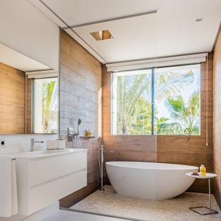 Foto de cuarto de baño principal, actual, grande, con armarios con paneles lisos, puertas de armario blancas, bañera exenta, combinación de ducha y bañera, paredes blancas, lavabo suspendido y ducha abierta