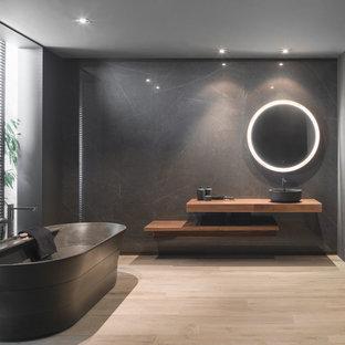 Foto de cuarto de baño principal, minimalista, con bañera exenta, paredes negras, suelo de madera clara, lavabo sobreencimera, suelo beige, armarios abiertos, puertas de armario de madera oscura, encimera de madera y encimeras marrones