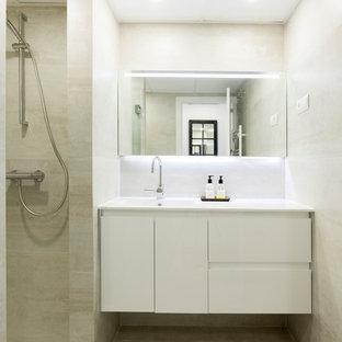 Modelo de cuarto de baño con ducha, actual, con puertas de armario blancas, baldosas y/o azulejos beige, ducha abierta, encimeras blancas, armarios con paneles lisos, paredes beige, lavabo integrado y suelo beige