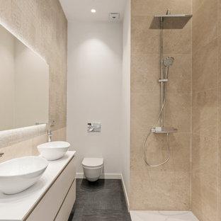 Modelo de cuarto de baño con ducha, actual, grande, con armarios con paneles lisos, puertas de armario blancas, ducha esquinera, sanitario de pared, baldosas y/o azulejos beige, baldosas y/o azulejos de porcelana, paredes blancas, lavabo sobreencimera, suelo gris, ducha abierta y encimeras blancas