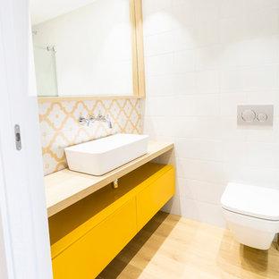 Immagine di una stanza da bagno scandinava con ante gialle, pareti bianche, top in legno, ante lisce, WC sospeso, piastrelle multicolore, piastrelle bianche, piastrelle gialle, parquet chiaro e lavabo a bacinella
