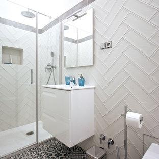 Diseño de cuarto de baño con ducha, nórdico, con puertas de armario blancas, encimeras blancas, sanitario de pared, baldosas y/o azulejos grises, baldosas y/o azulejos blancos, suelo multicolor y ducha con puerta con bisagras