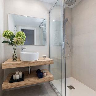 Modelo de cuarto de baño escandinavo con armarios abiertos, ducha empotrada, baldosas y/o azulejos beige, lavabo sobreencimera, encimera de madera, suelo beige, ducha con puerta con bisagras y encimeras beige