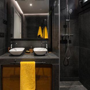 Foto de cuarto de baño contemporáneo, de tamaño medio, con armarios con paneles lisos, puertas de armario marrones, ducha abierta, baldosas y/o azulejos negros, baldosas y/o azulejos de porcelana, lavabo sobreencimera, suelo marrón y encimeras negras