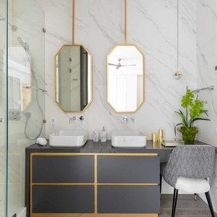 Modelo de cuarto de baño con ducha, actual, con armarios tipo mueble, puertas de armario grises, ducha empotrada, baldosas y/o azulejos blancos, paredes blancas, lavabo sobreencimera, ducha con puerta con bisagras y encimeras grises