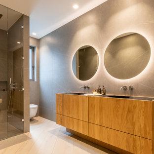 Foto de cuarto de baño con ducha, actual, grande, con armarios con paneles lisos, puertas de armario de madera oscura, ducha empotrada, baldosas y/o azulejos grises, lavabo integrado, suelo beige, ducha con puerta con bisagras y encimeras negras