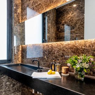 Diseño de cuarto de baño actual, grande, con puertas de armario negras, baldosas y/o azulejos marrones, lavabo integrado, suelo gris y encimeras negras